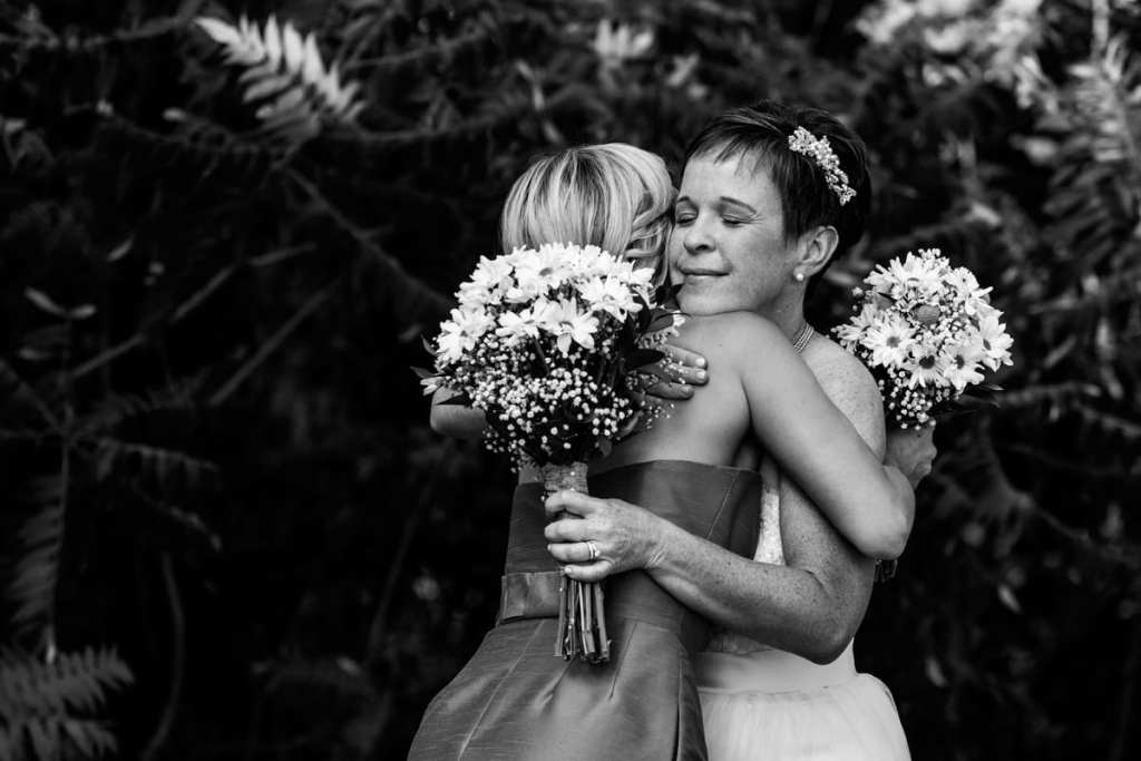bride and bridesmaid hugging holding bouquets of daisies