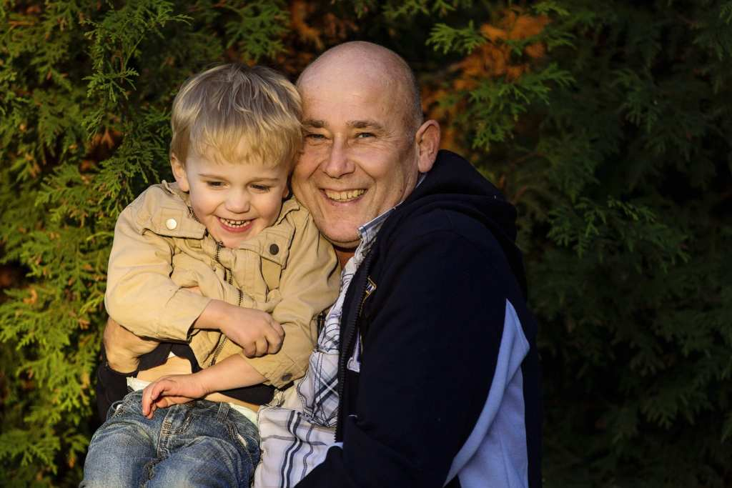 little boy in beige jacket sitting on dad's lap in rural Cornwall family shoot