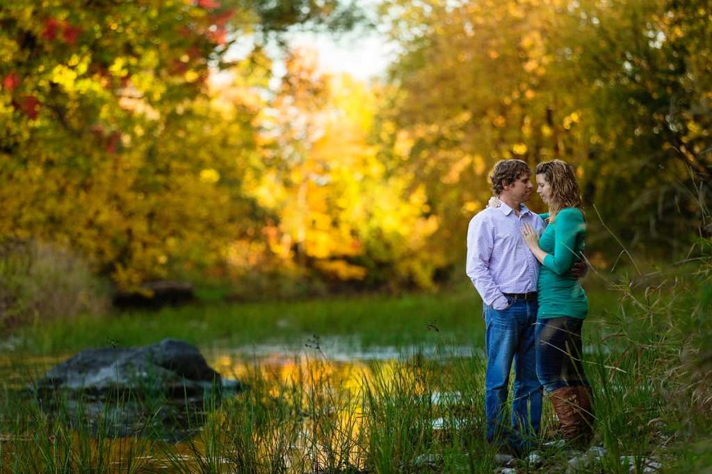 woman in bright green sweater and man in button up shirt in fall engagement session