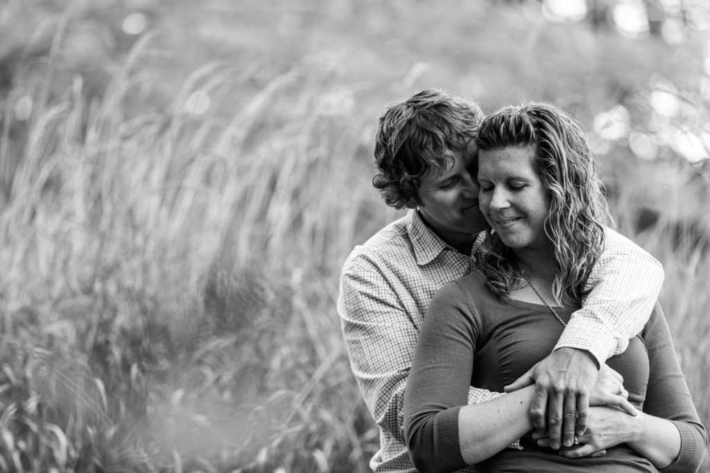 couple cuddling in tall grass in rural Martintown engagement session