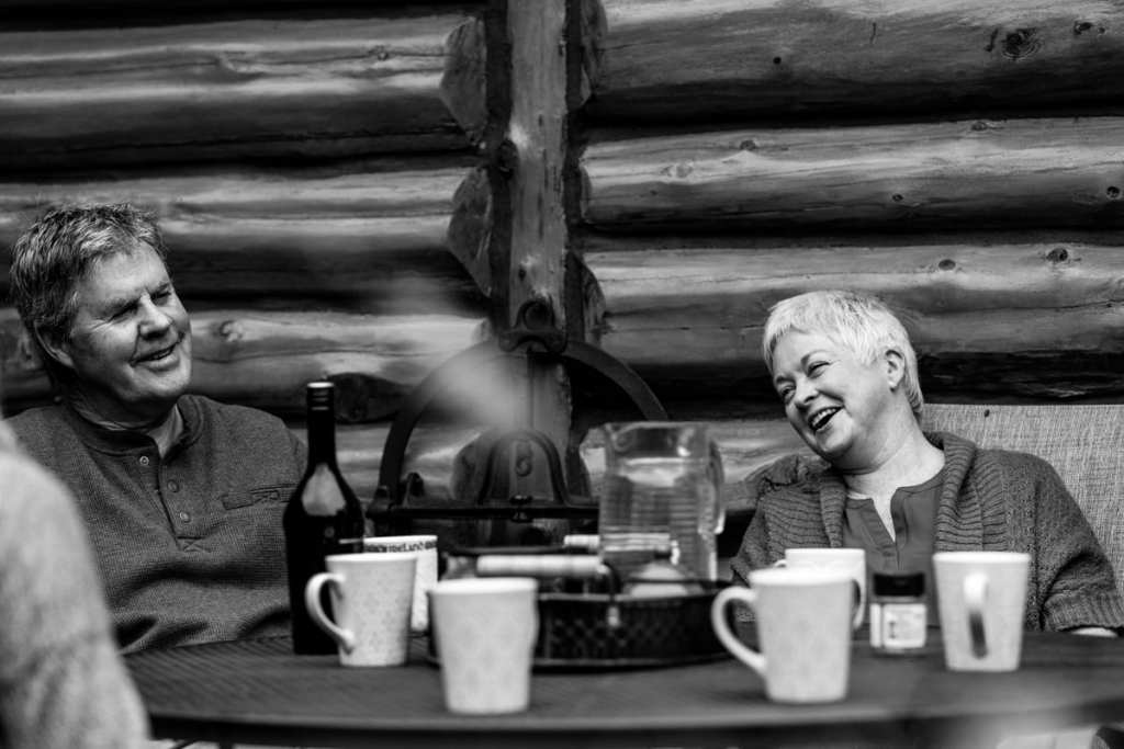 mom and dad laughing over coffee on outdoor patio of log cabin