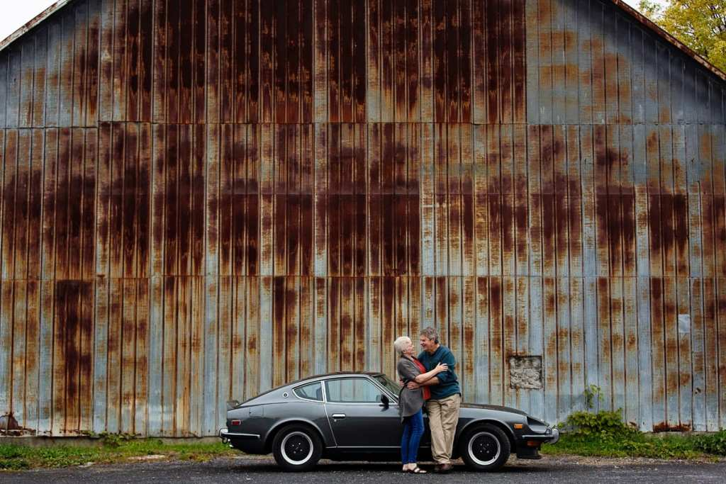 gritty tin wall background and couple with classic car in casual ontario portrait