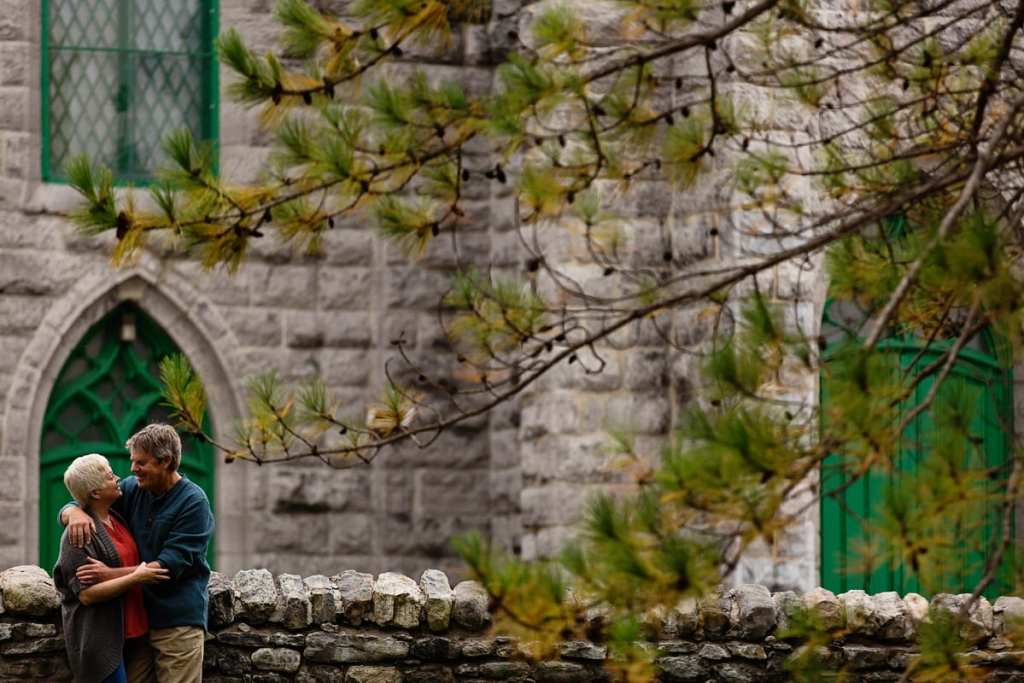 Couple leaning on aged stone wall in front of church
