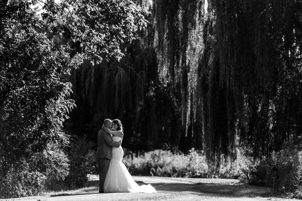 bride and groom hug under willow trees on bicycle path
