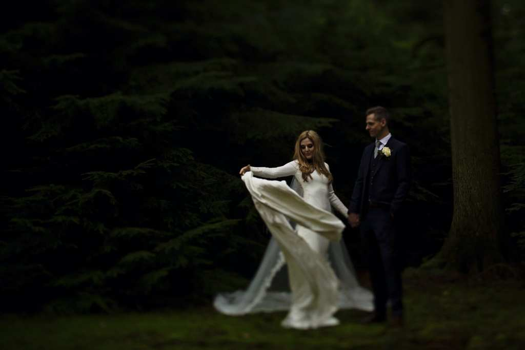 bride flings dress dramatically in pine grove on Rhinefield Ornamental Drive during New Forest wedding portraits
