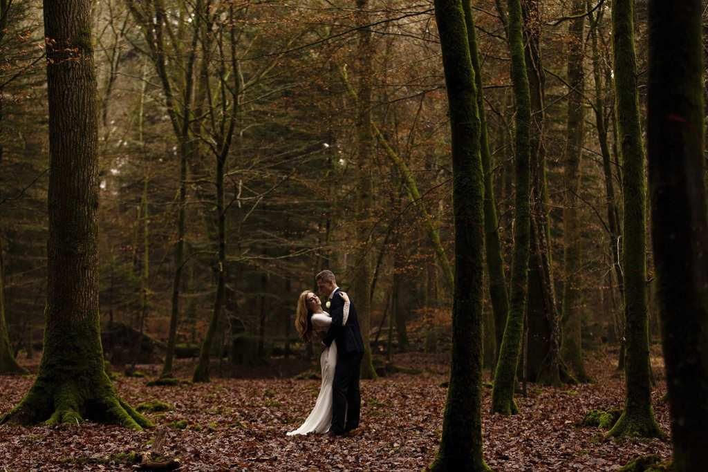 bride and groom cuddle amongst tall trees on Rhinefield Ornamental Drive during chic New Forest wedding portraits