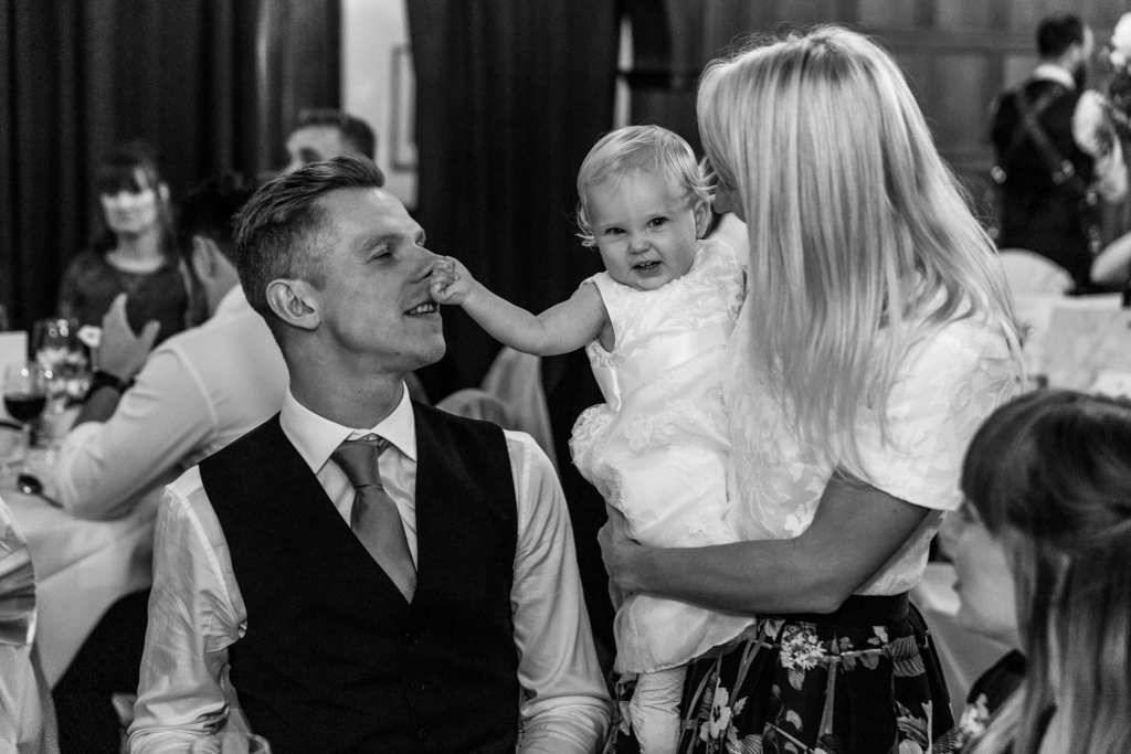 woman stands and holds little girl in white dress who squeezes groom's nose during wedding reception at Rhinefield House