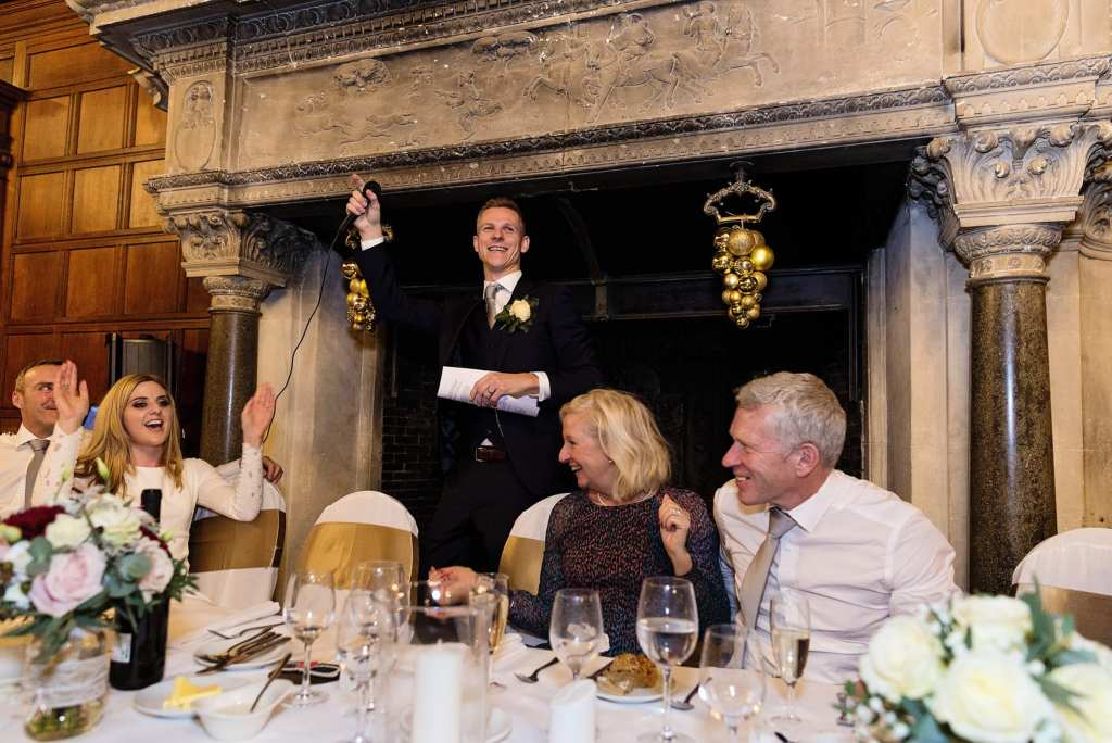 Groom holds mic in the air during speech while bride waves arms in the air from her seat during wedding reception at Rhinefield House