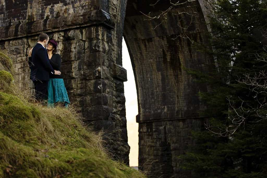 couple cuddle under arch of Llanberis viaduct during Snowdonia portrait session