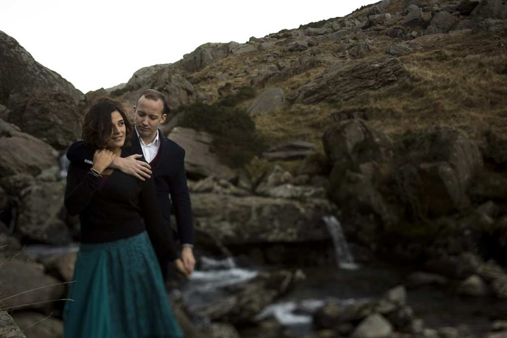 man holds wife next to river during Snowdonia portrait session