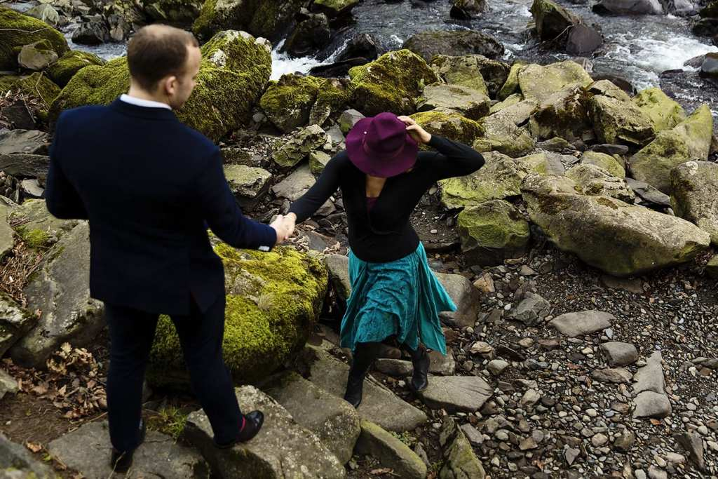 Man gives wife in purple hat a hand while walking up stone steps by river
