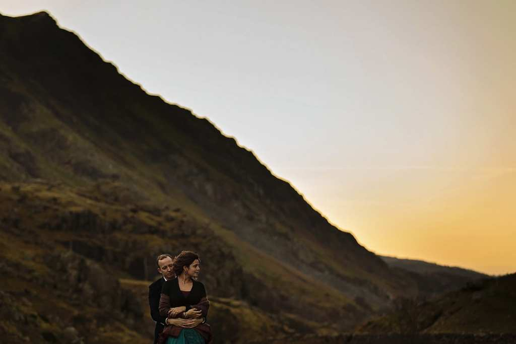 couple stand in valley at dusk looking opposite ways during snowdonia portrait session