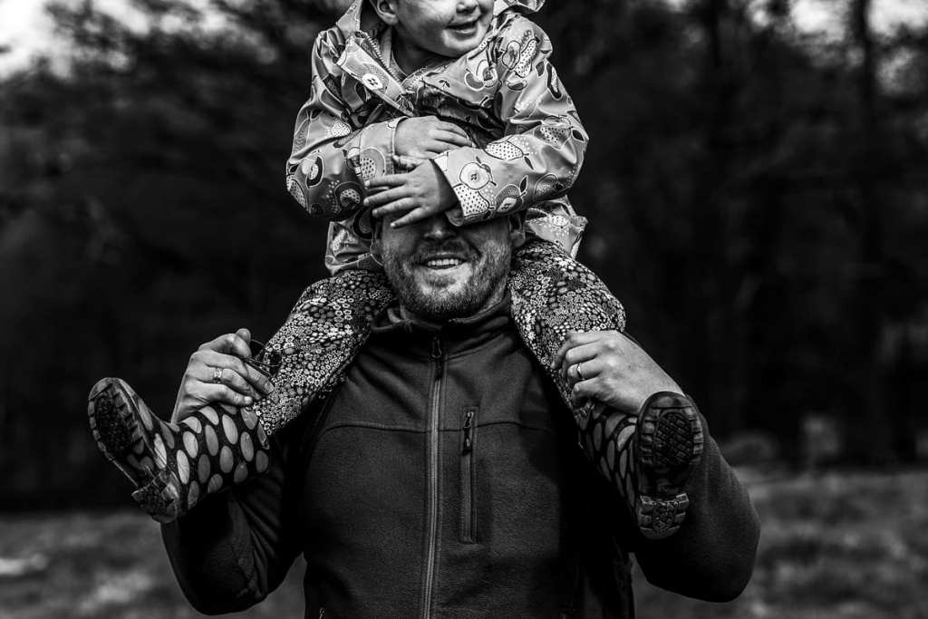 girls covers dad's face while riding on his shoulders