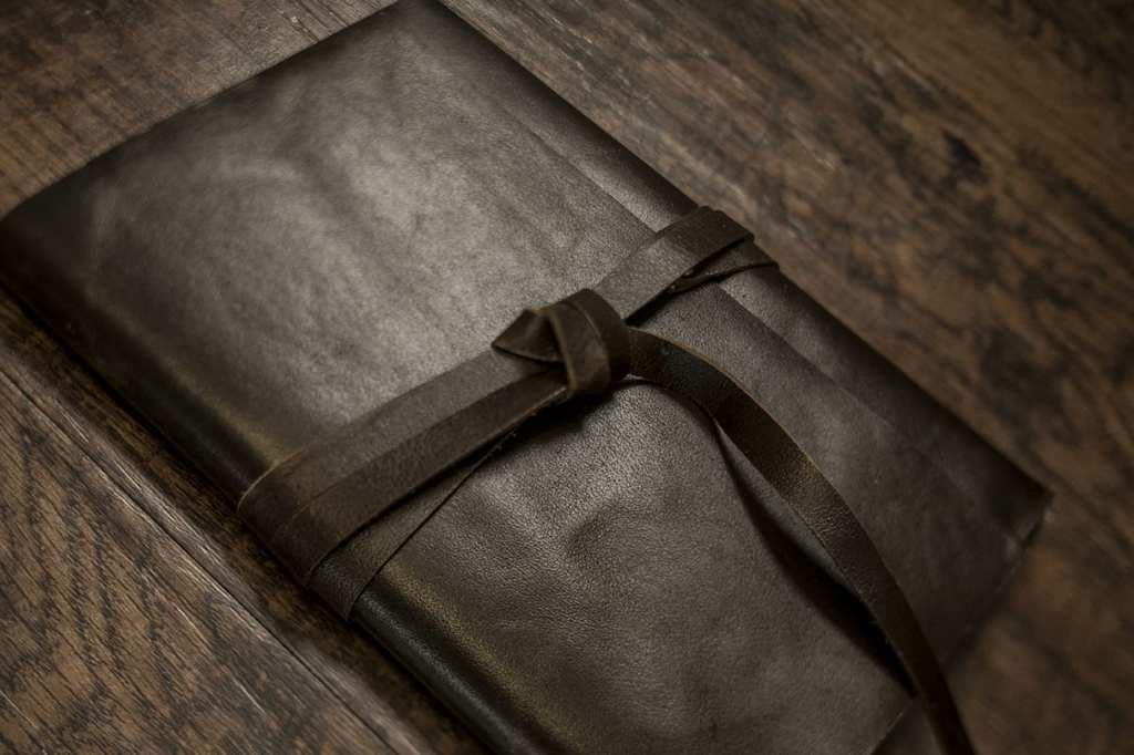 leather strap wrapped around dark leather photo holding modern ontario wedding photos