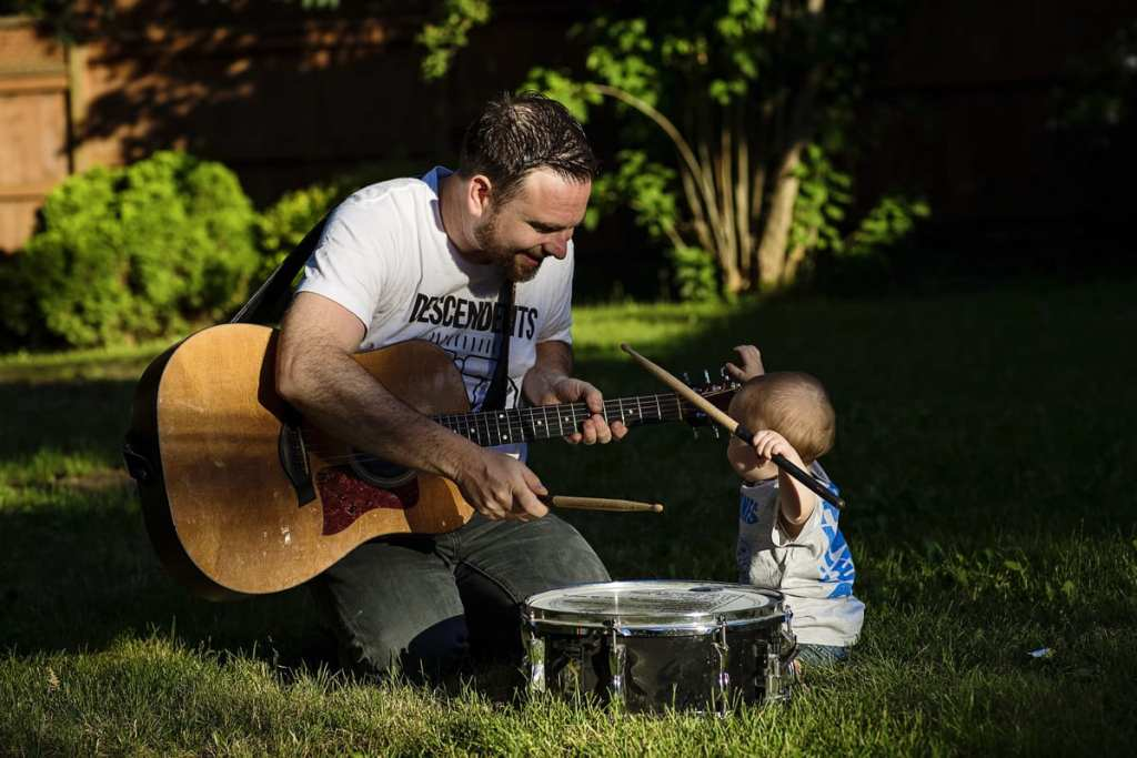father with guitar helps son play drums in sunshine
