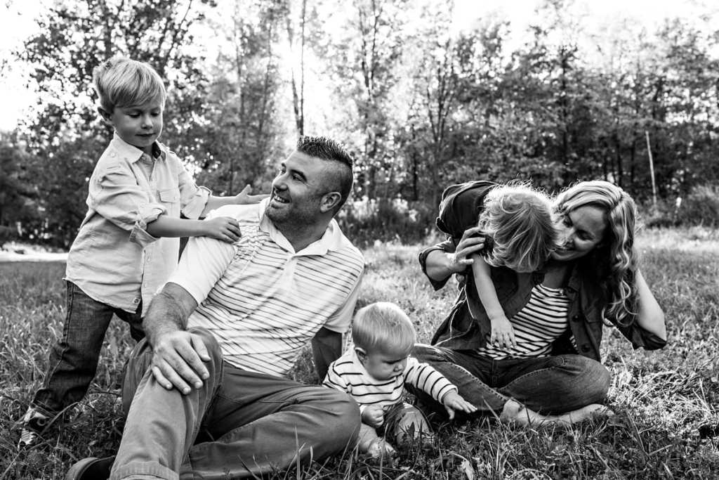 three boys climb on parents who are sitting in grass during session with Ontario family photographer