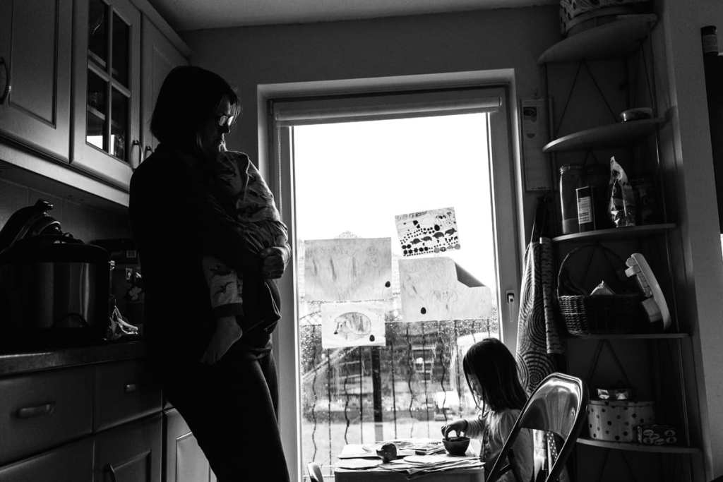 mother holds child in window light while looking down at daughter