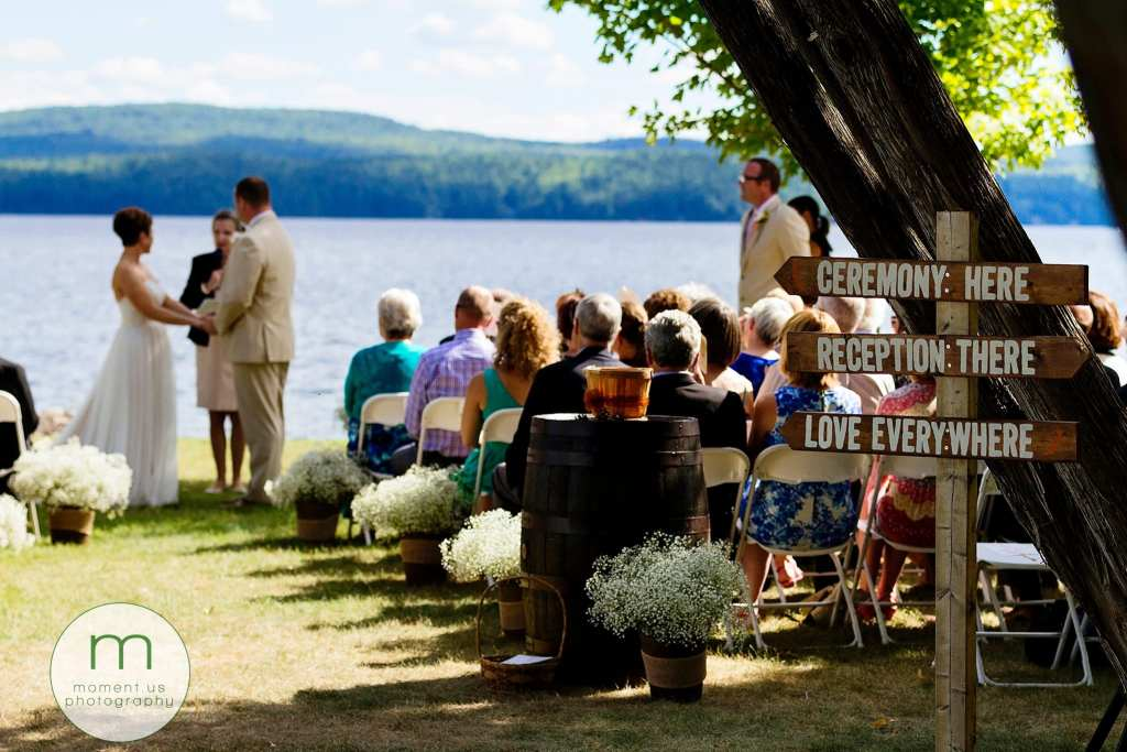 love is everywhere sign at end of aisle while bride and groom get married during waterfront Lake Calabogie wedding