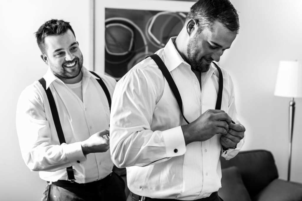 best man helps groom with suspenders during preparations for Autumnal NAV Centre Cornwall Wedding