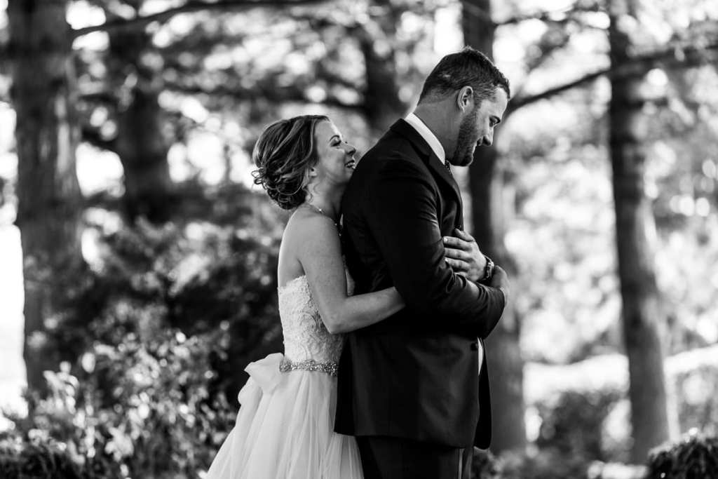 bride hugs groom from behind during first look for Autumnal NAV Centre Cornwall Wedding
