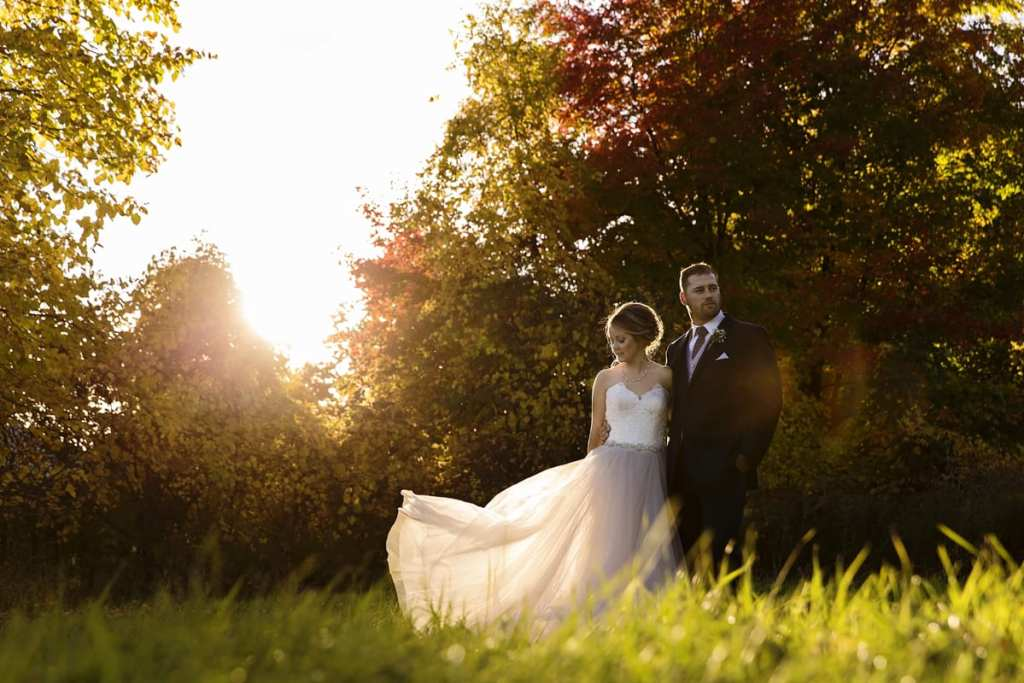bride in blush wedding gown stands with groom in field for Autumnal NAV Centre Cornwall Wedding