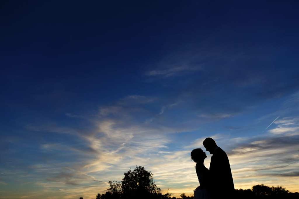 bride and groom in silhouette against blue and yellow sunset