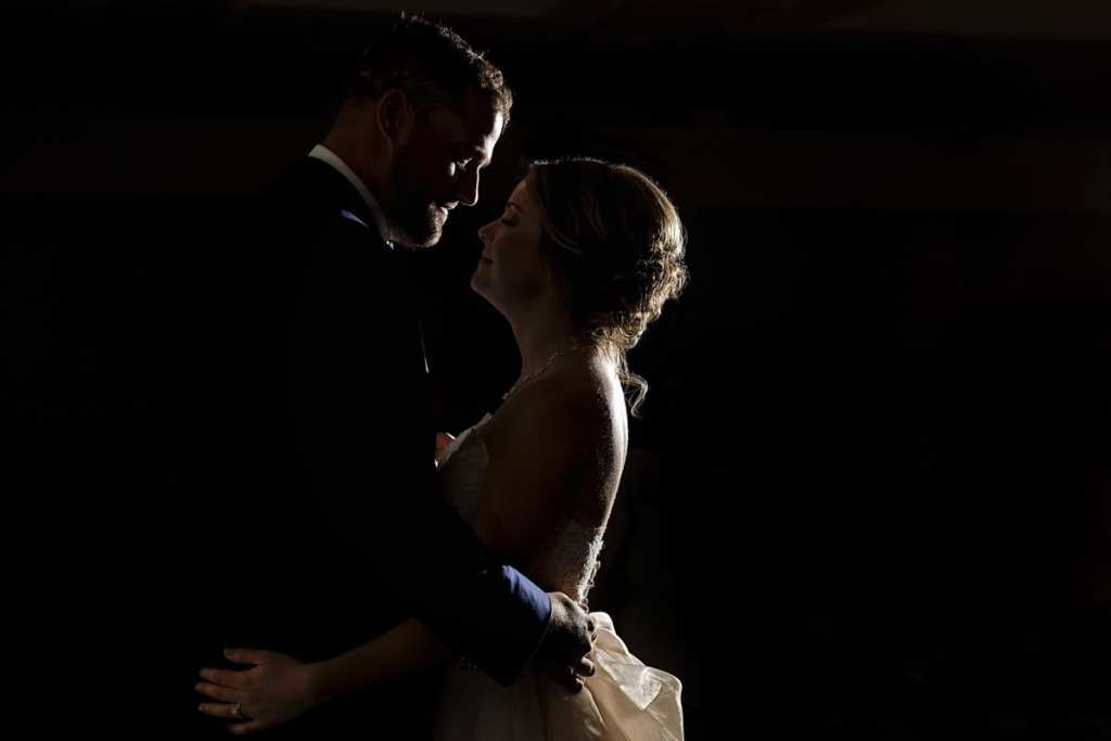 bride and groom in rim light during first dance at their Autumnal NAV Centre Cornwall Wedding