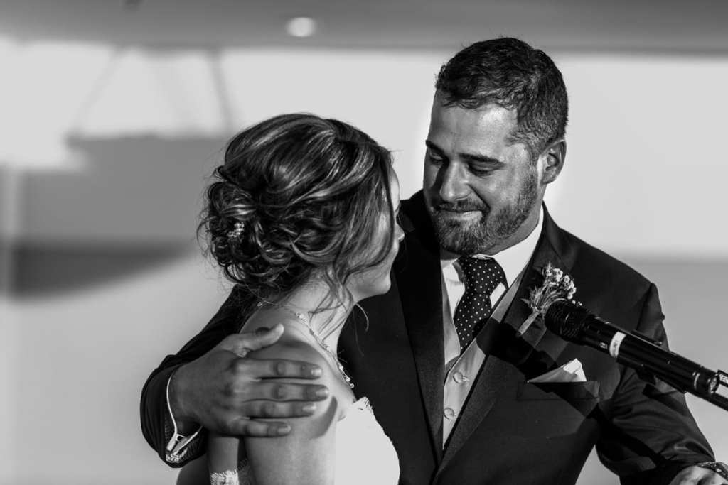 groom holding bride and looking at her during speeches for Autumnal NAV Centre Cornwall Wedding