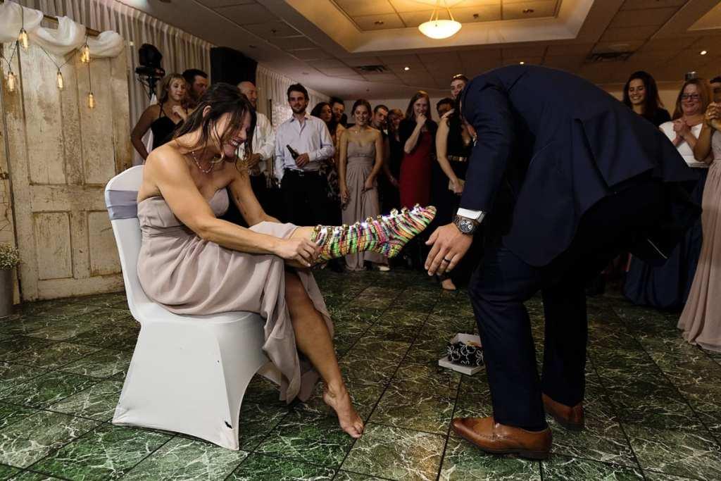 groom helping sister put on lighted socks during Autumnal NAV Centre Cornwall Wedding reception