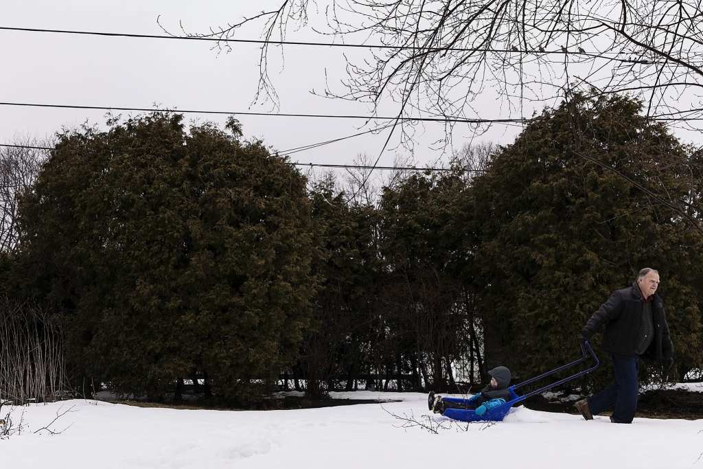 boy rides around yard on shovel while being pulled by grandpa during during Ontario Family Photojournalism session