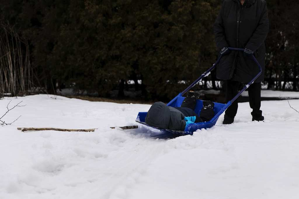 boy faceplants on shovel while getting rides around yard during Ontario Family Photojournalism session