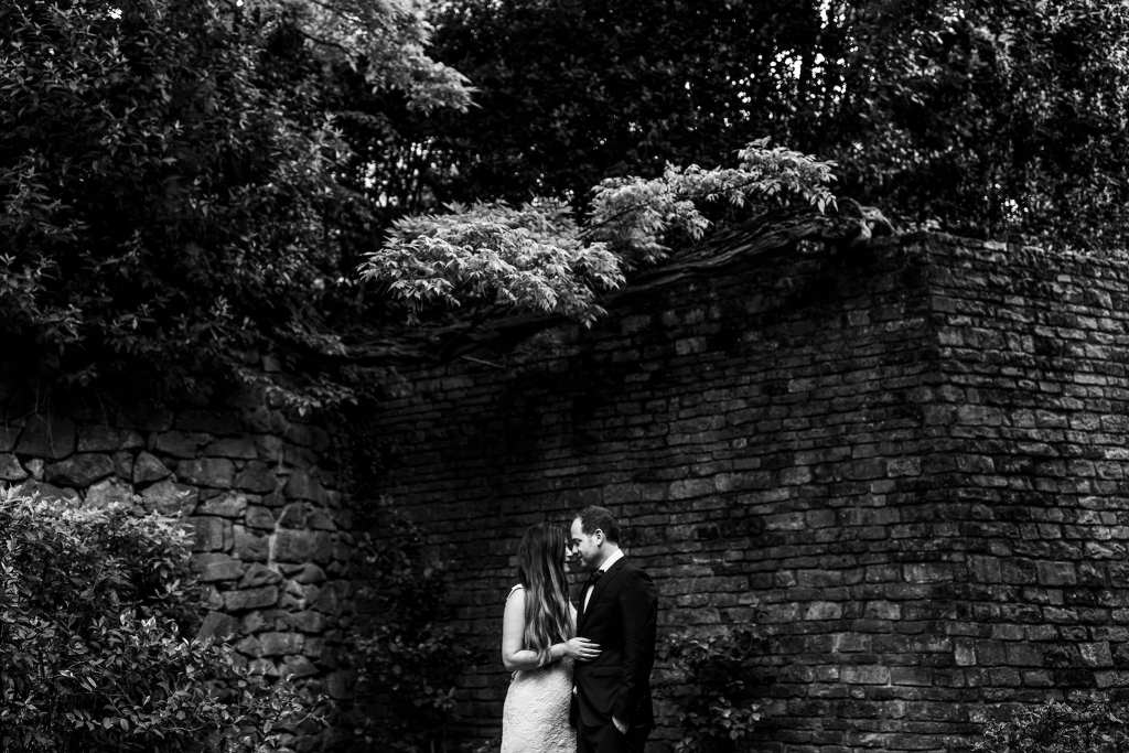bride and groom hold one another in front of Italian villa's stone wall covered in ivy during session with Ontario & Destination Wedding Photographer