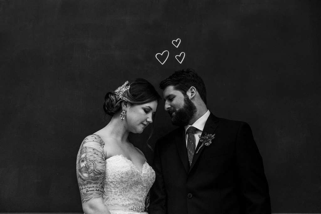 couple stand together under hearts drawn on chalkboard before intimate cornwall wedding ceremony