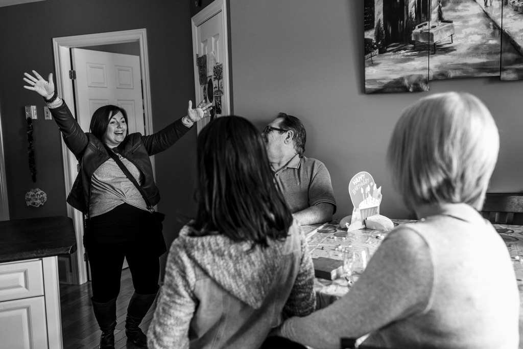 woman enters room with wild gestures of surprise during Eastern Ontario family photojournalism session