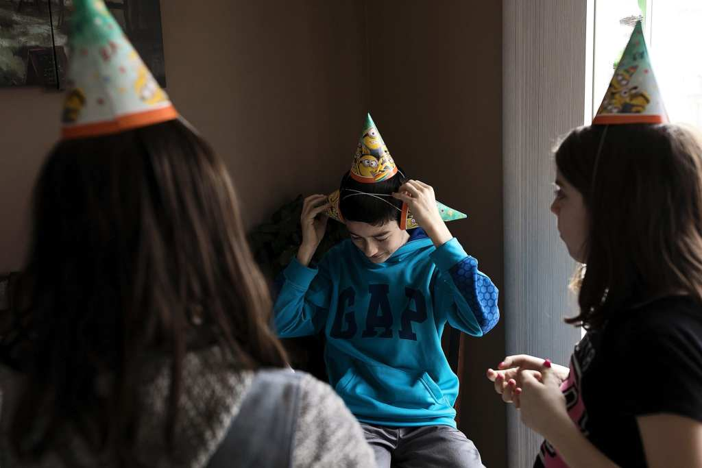 boy put three party hats on head during Eastern Ontario family photojournalism session