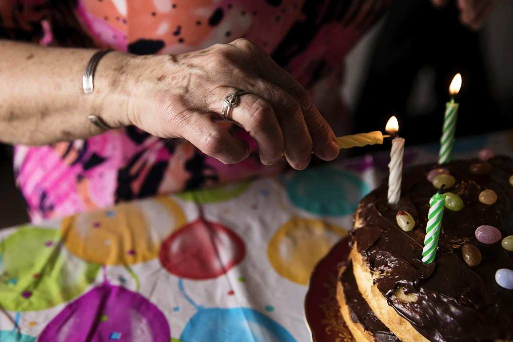 grandma lighting birthday candles on birthday cake during Eastern Ontario family photojournalism session