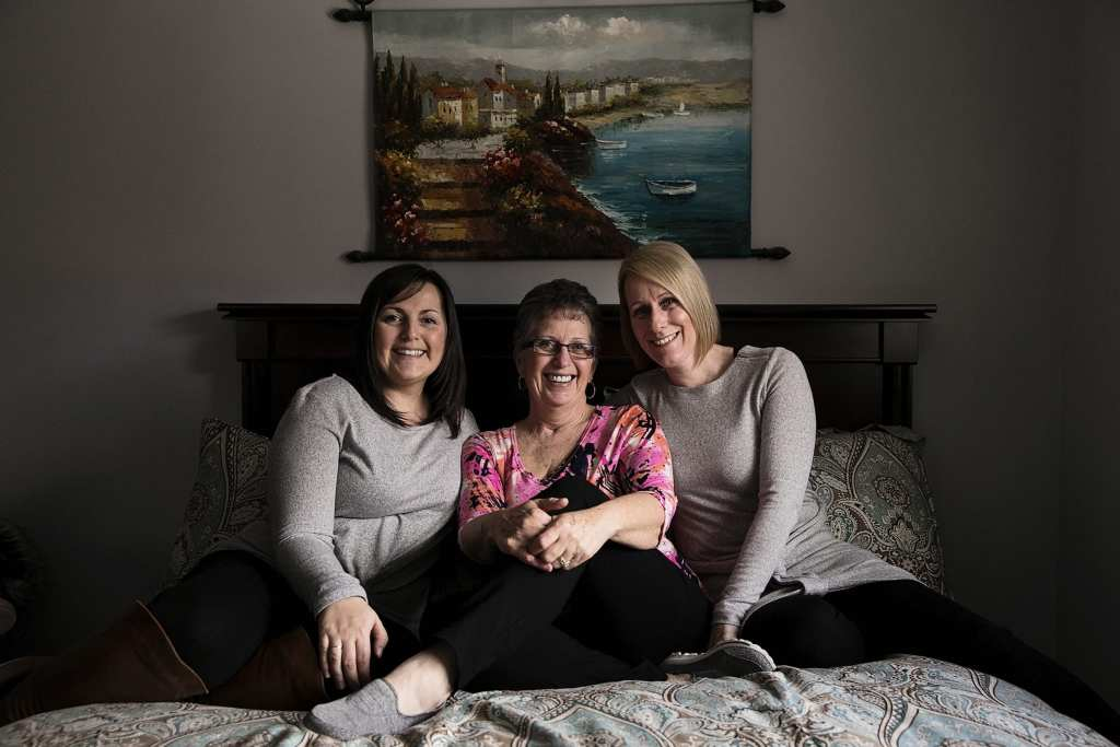 mother with two daughters sitting on bed