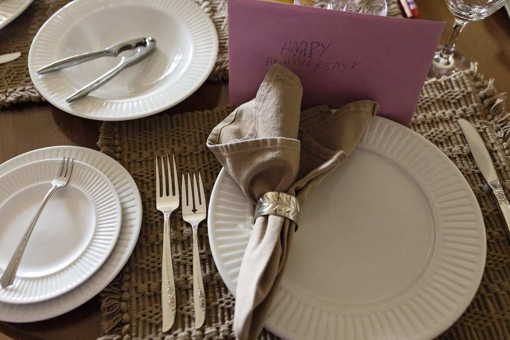 table laid with anniversary cards and fancy place settings for lobster dinner