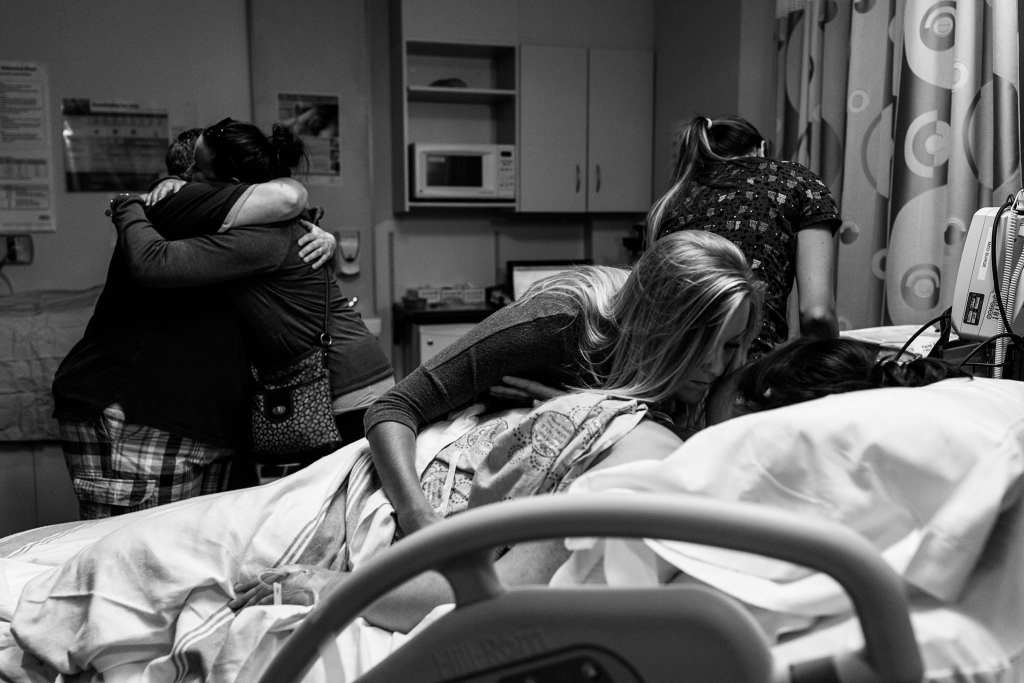 family and friends hug in hospital room