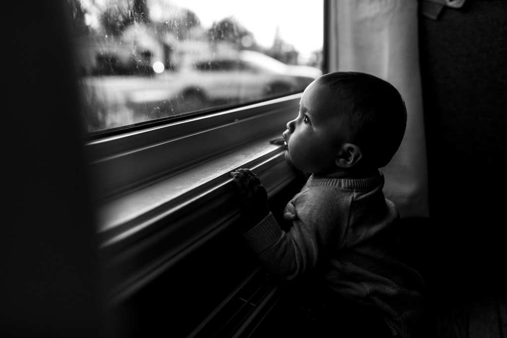 baby stands at window and looks outside