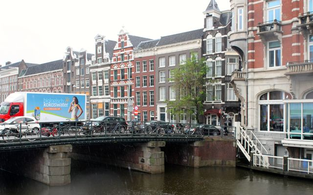Amsterdam canal with bridge and monumental buildings.