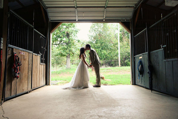 Bride and Groom kiss in a barn