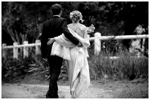 Bride and groom take a romantic walk in the rain