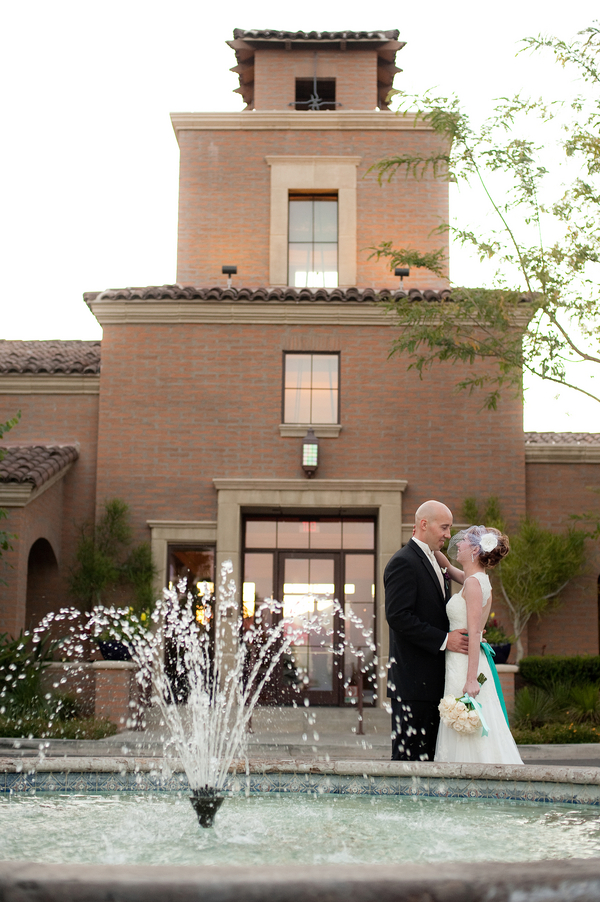bride and groom embrace near a fountain