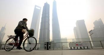 A woman covers her nose and mouth with her scarf amid heavy haze, as she rides a bicycle at the Pudong financial area in Shanghai, February 12, 2015.