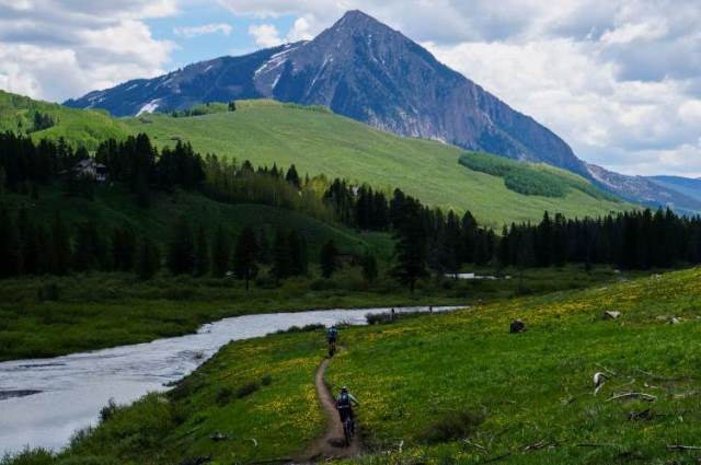 Two riders on the Lower Loop singletrack along the Slate River with Crested Butte in background