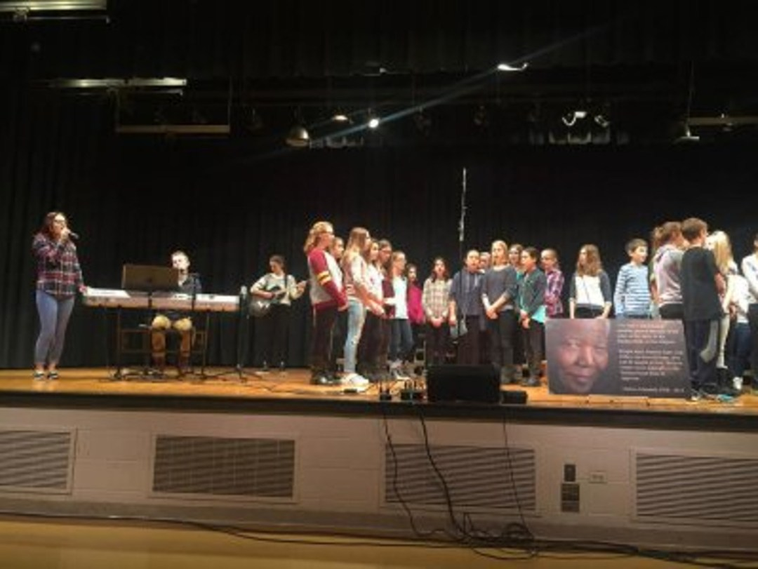 MWAH! Performing Arts Troupe members Lindsay Kent (from far left), Justin Smusz, and Taylor Oechsel on December 5 join a choral ensemble from Churchville Middle School in Elmhurst in the song 'Nothing More,' focusing on a quote by Nelson Mandela. (Photo by Jennifer Kent)