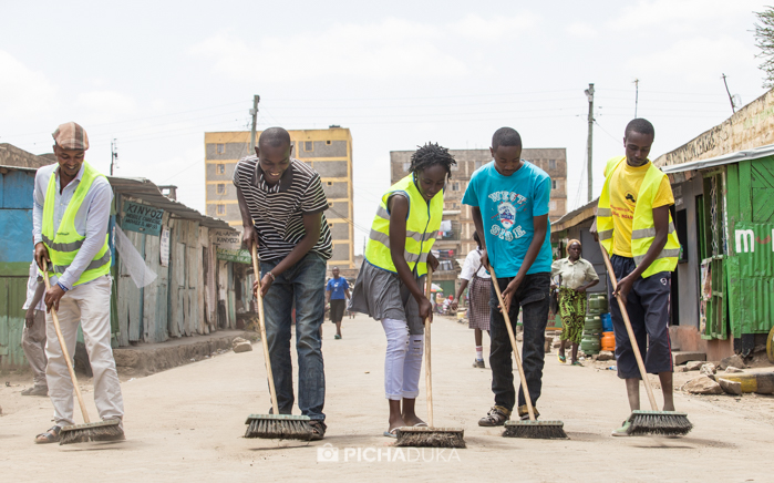 Members of Wasafi Organisation sweep the street outside their Ukoo Flani base in Dandora.