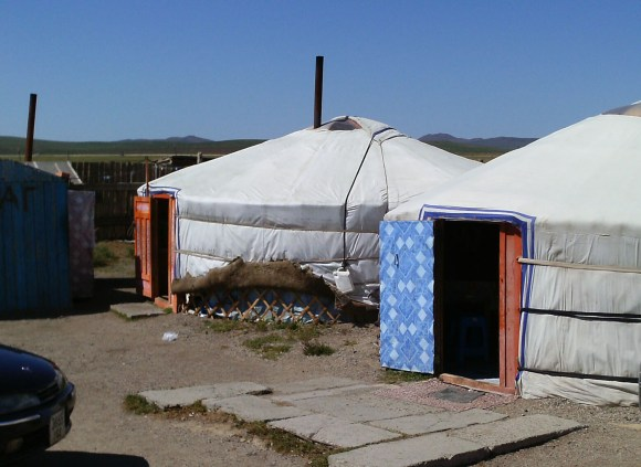 PHOTO: Two Mongolian ger, semi-permanent, circular tent structures, complete with welcome mats at the doors.