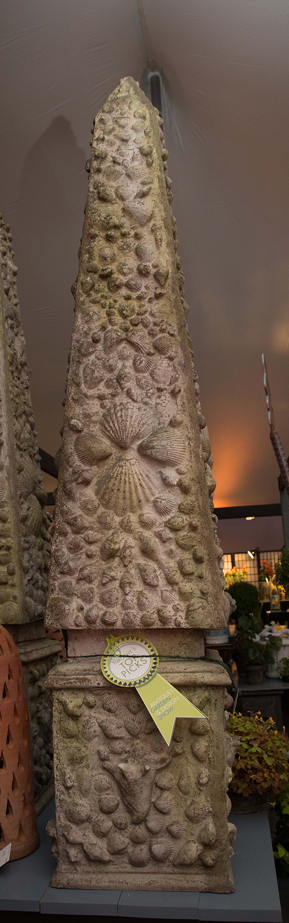 Booth #310, Craig Bergmann Landscape Design: A towering garden obelisk with raised shell motif.